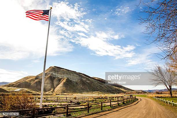 low angle view of american flag over dirt road, painted hills, oregon, united states - flagpole stock pictures, royalty-free photos & images