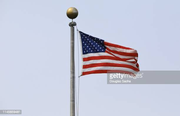 low angle view of american flag waving against clear blue sky - flagpole stock pictures, royalty-free photos & images