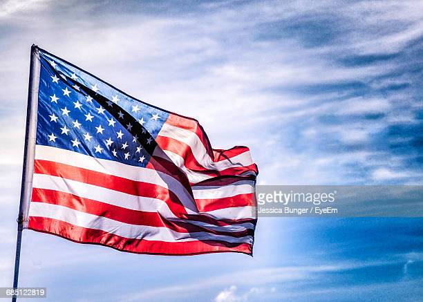 low angle view of american flag waving against sky - national flag stock photos and pictures