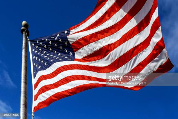 low angle view of american flag waving against sky - stars and stripes stock pictures, royalty-free photos & images