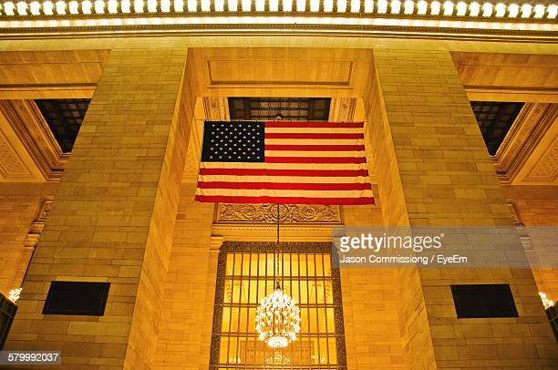 low angle view of american flag with illuminated chandelier in grand central station - グランドセントラル駅 ストックフォトと画像
