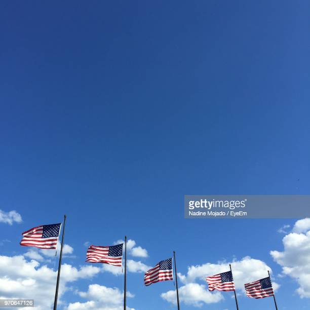 low angle view of american flags against blue sky - mojado stock pictures, royalty-free photos & images