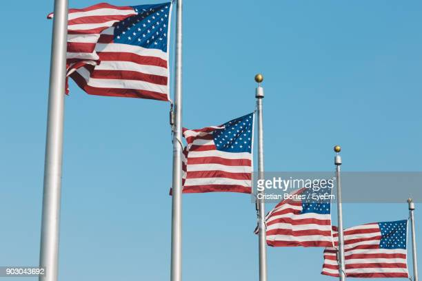 low angle view of american flags fluttering against clear blue sky - flagpole stock pictures, royalty-free photos & images