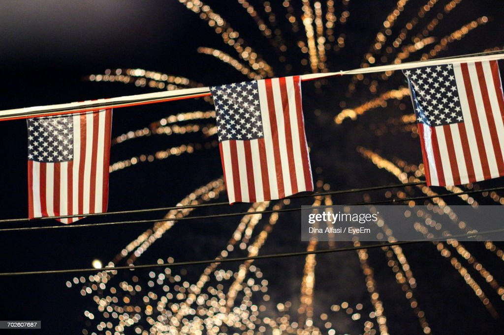 Low Angle View Of American Flags Hanging Against Firework Display At Night : Stock Photo