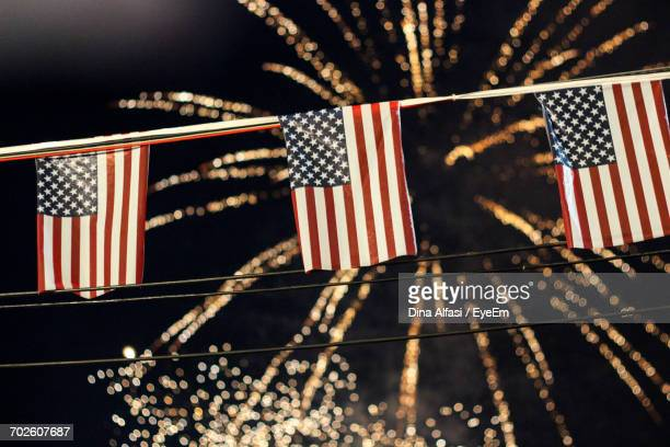 low angle view of american flags hanging against firework display at night - independence day holiday stock pictures, royalty-free photos & images