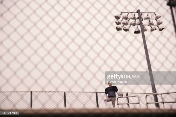 low angle view of american football player looking away while standing in stadium seen through fence - american football strip stock pictures, royalty-free photos & images