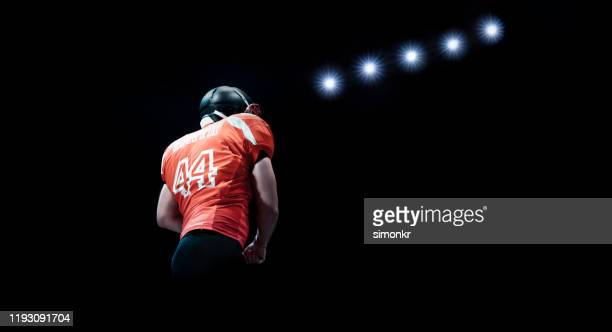 low angle view of american football player - safety american football player stock pictures, royalty-free photos & images
