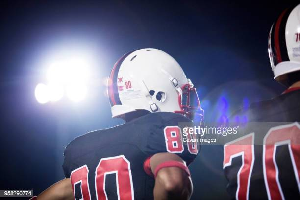 low angle view of american football players against sky at night - high school football stock pictures, royalty-free photos & images