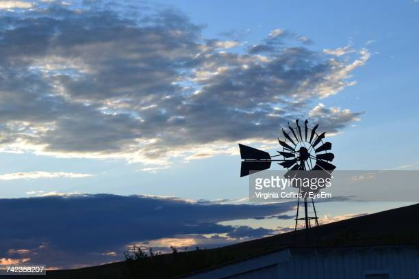 low angle view of american-style windmill on hill against sky during sunset - american style windmill stock pictures, royalty-free photos & images
