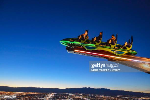 low angle view of amusement park against clear blue sky - las vegas stock pictures, royalty-free photos & images