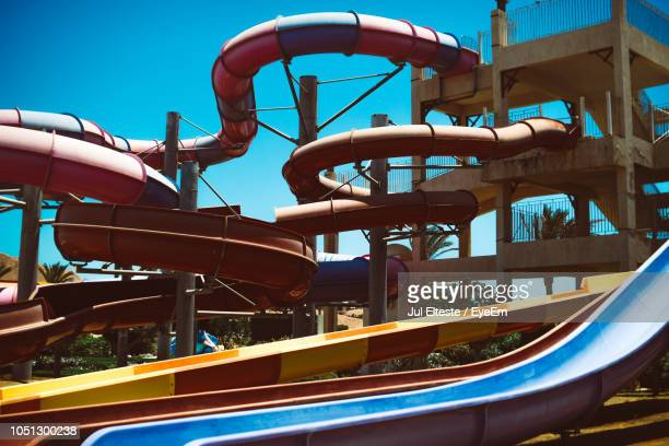 Low Angle View Of Amusement Park Ride Against Blue Sky During Sunny Day