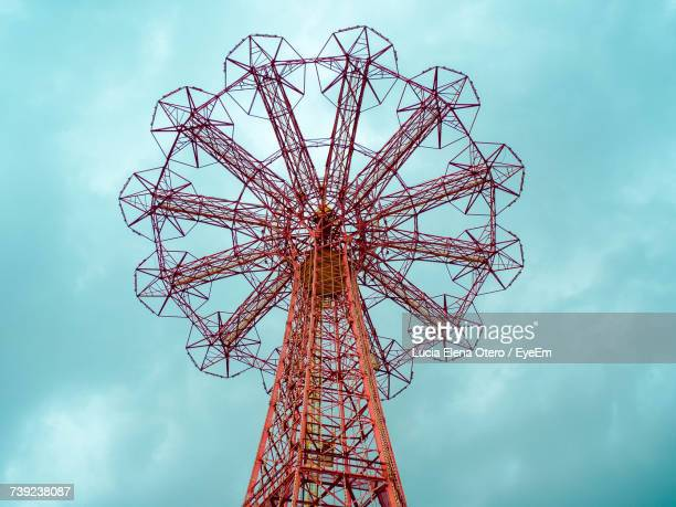 low angle view of amusement park ride against sky - coney island stock pictures, royalty-free photos & images