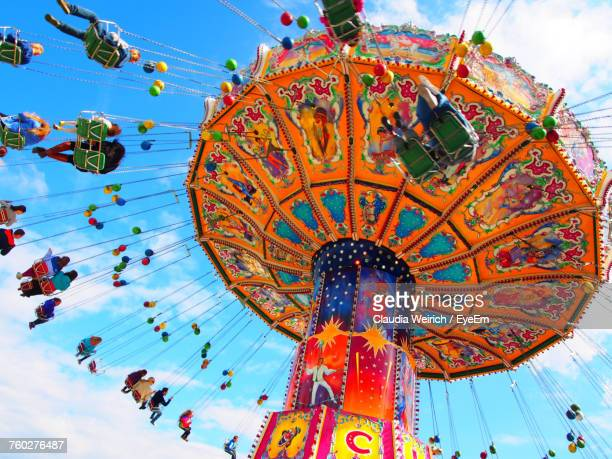 low angle view of amusement park ride against sky - carnival stock photos and pictures