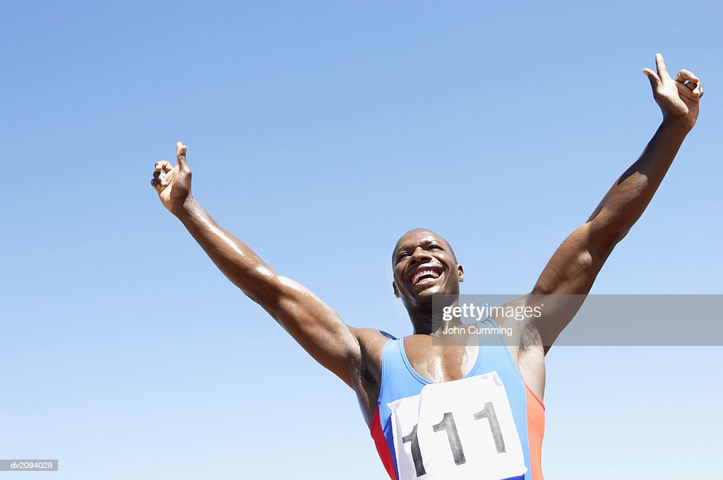 Low Angle View of an Athlete Celebrating With His Arms Upstretched : Stock Photo