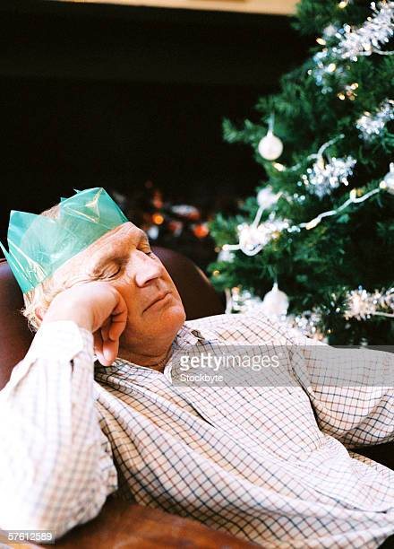 Low angle view of an elderly man sleeping in a chair next to a Christmas tree