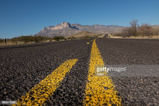 A low angle view of an empty US180 highway and the landscape of the Guadalupe mountains near the New Mexico border Texas