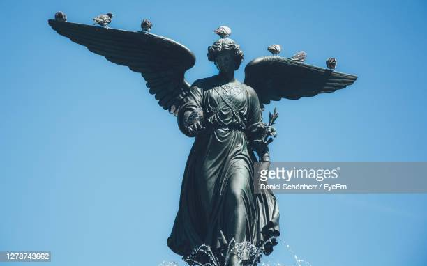 low angle view of angel statue against clear blue sky - bethesda maryland stock pictures, royalty-free photos & images