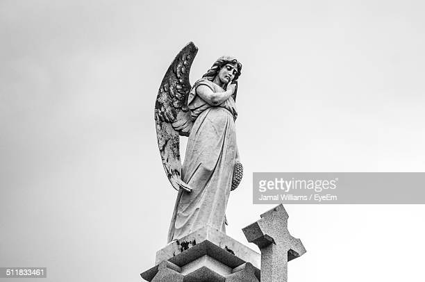 low angle view of angel statue and cross shape - female likeness stock pictures, royalty-free photos & images