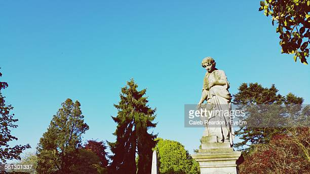 Low Angle View Of Angel Statue At Cemetery Against Clear Blue Sky
