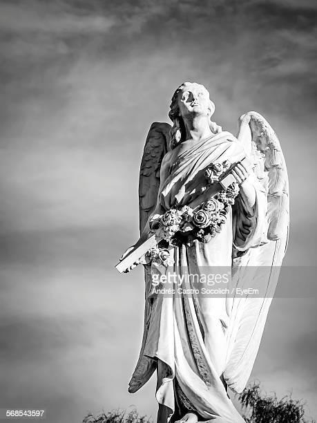 Low Angle View Of Angel Statue At Cemetery Against Sky
