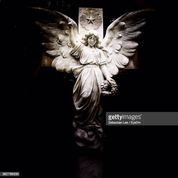 Low Angle View Of Angel Statue On Cross