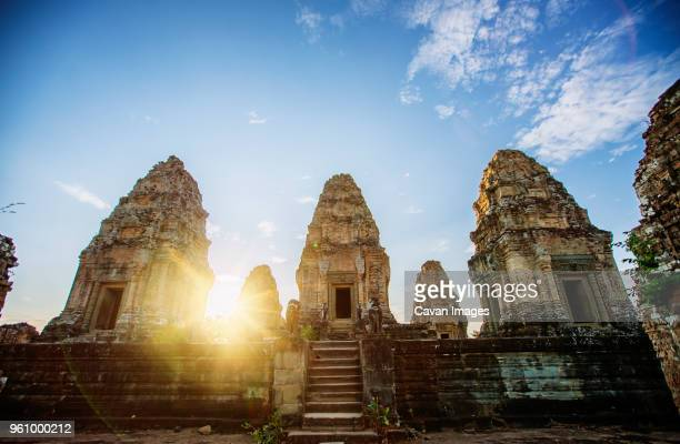 low angle view of angkor wat temple against sky during sunset - アンコールワット ストックフォトと画像