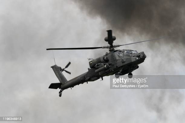 low angle view of apache helicopter in flying in sky - apache helicopter stock pictures, royalty-free photos & images