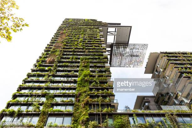 low angle view of apartment building with vertical garden and heliostat, sky background with copy space - solar mirror stock pictures, royalty-free photos & images