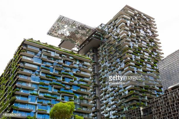 low angle view of apartment buildings swith vertical gardens and heliostat, sky background with copy space - building exterior stock pictures, royalty-free photos & images
