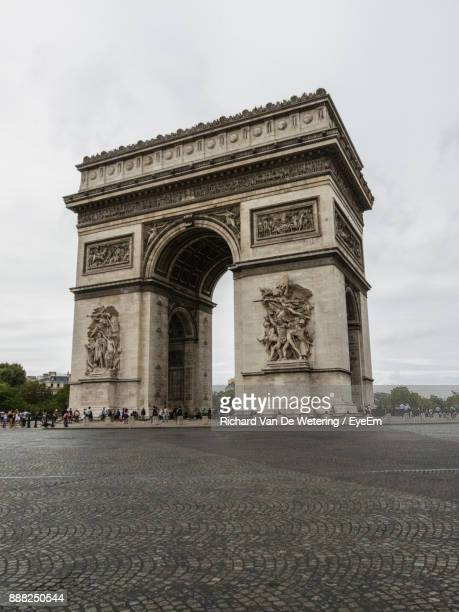 low angle view of arc de triomphe against cloudy sky - triumphal arch stock photos and pictures