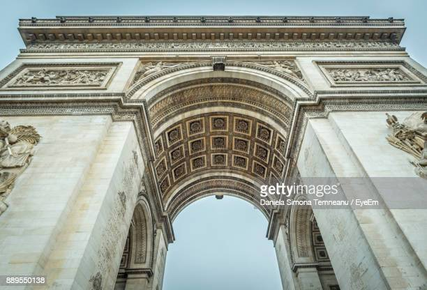 low angle view of arc de triomphe against sky - パリ凱旋門 ストックフォトと画像
