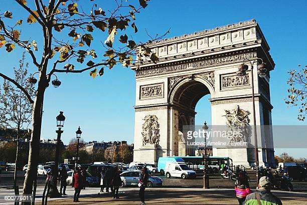 Low Angle View Of Arc De Triomphe By Road Against Blue Sky