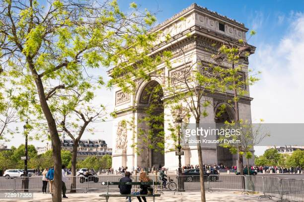 low angle view of arc de triomphe by road against blue sky - シャンゼリゼ通り ストックフォトと画像