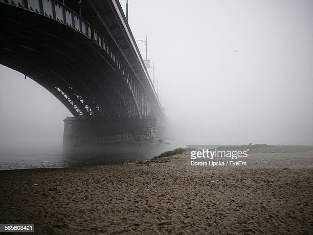 low angle view of arch bridge by sandy riverbank on foggy day - flussufer stock-fotos und bilder