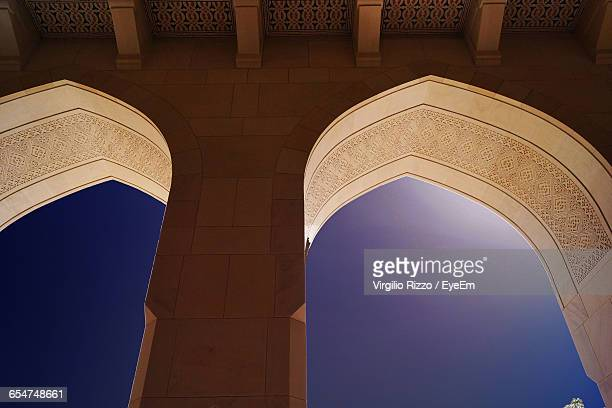 low angle view of arch windows of historic building against clear sky - boog architectonisch element stockfoto's en -beelden