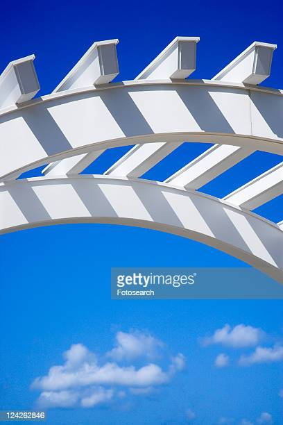 Low angle view of arched white arbor with blue sky.
