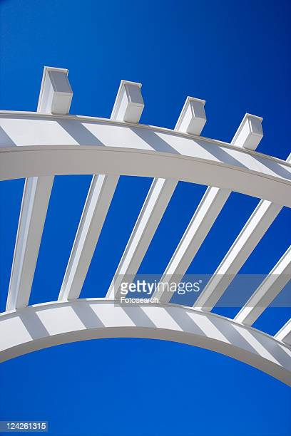 Low angle view of arched white trellis with blue sky.
