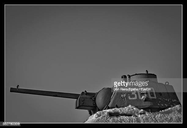 Low Angle View Of Armored Tank On Snowcapped Field Against Clear Sky