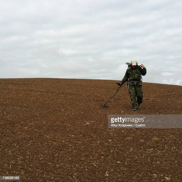 low angle view of army soldier using metal detector on field against cloudy sky - responsibility stock pictures, royalty-free photos & images