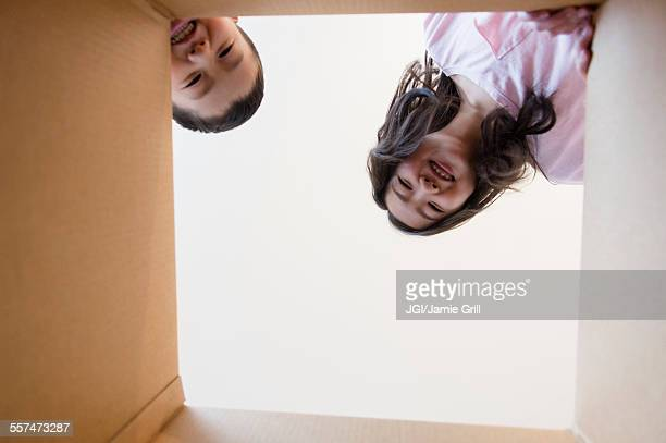 Low angle view of Asian brother and sister opening box