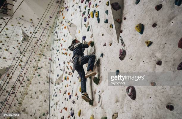 low angle view of athletic man climbing on the wall in a gym. - climbing stock pictures, royalty-free photos & images