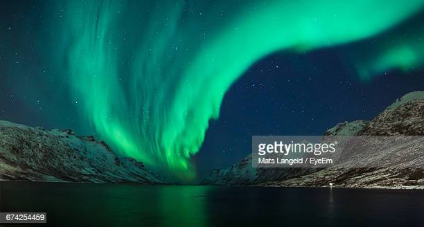 Low Angle View Of Aurora Borealis Over Lake And Mountains In Winter