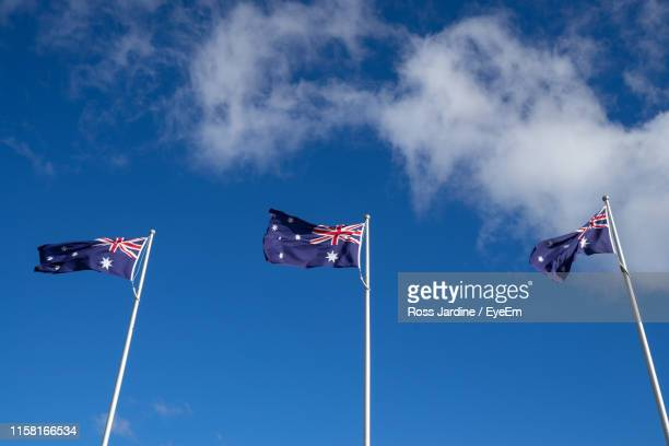 low angle view of australian flag against blue sky - australian flag stock pictures, royalty-free photos & images