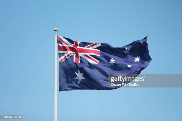 low angle view of australian flag against clear blue sky - australian flag stock pictures, royalty-free photos & images