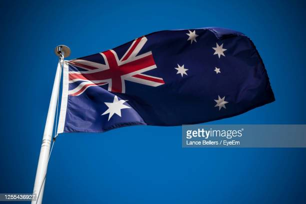 low angle view of australian flag against sky - australian flag stock pictures, royalty-free photos & images