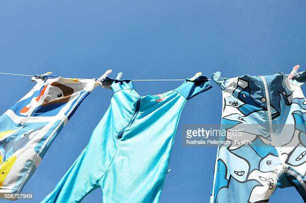 low angle view of baby clothing on clothesline - nathalie pellenkoft stock pictures, royalty-free photos & images