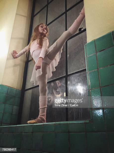 Low Angle View Of Ballerina Stretching On Window Sill