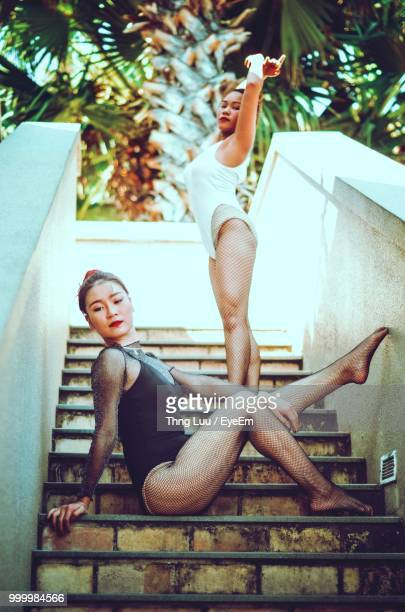 Low Angle View Of Ballet Dancers In Swimwear On Steps Against Trees