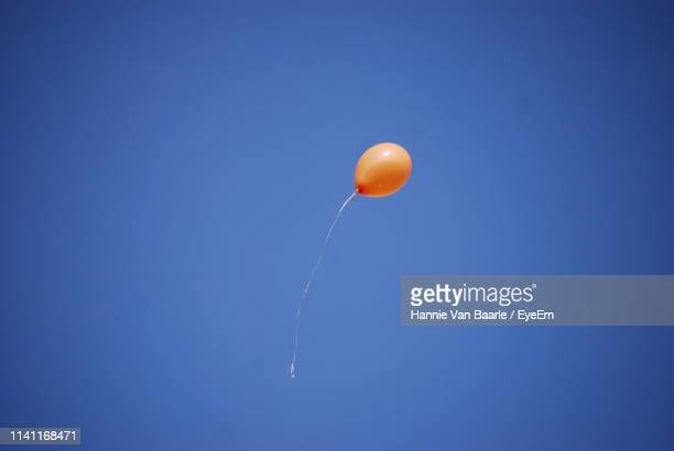 Low Angle View Of Balloon Flying Against Clear Blue Sky During Sunny Day