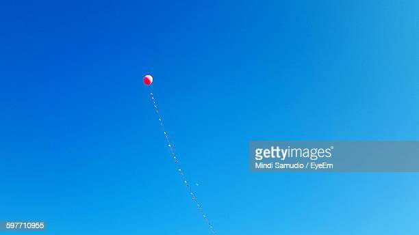 Low Angle View Of Balloon Flying In Clear Blue Sky